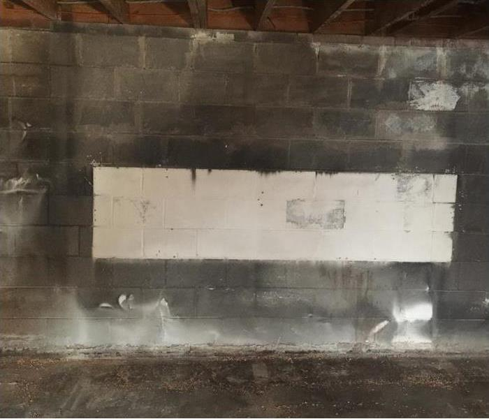 Smoke damage on a basement wall where fire began is almost black
