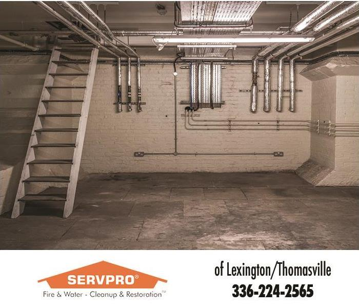 clean basement with plumbing and stair case that the walls have been waterproofed in white sealant