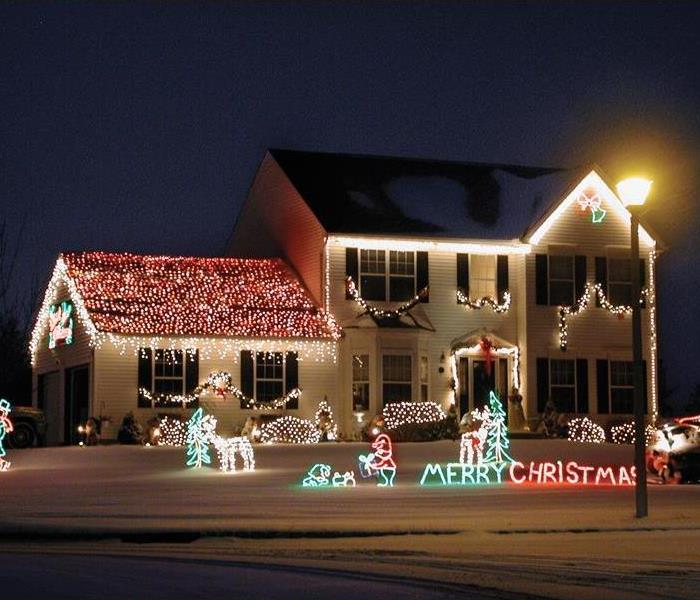 Two story family home and yard covered in snow, Christmas lights and yard decorations.